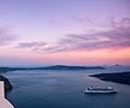 ship leaving santorini greece at sunset