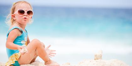 baby girl sitting on beach
