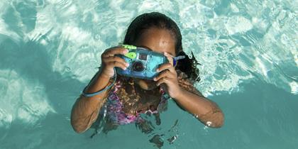girl with waterproof camera in pool
