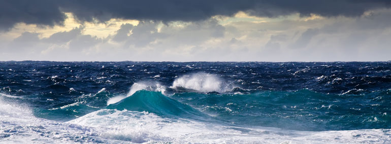 How do ships minimize the rocking from rough seas?